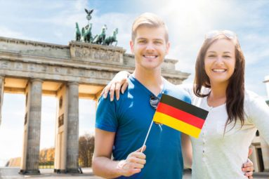Smiling Young Couple Holding Flag At Brandenburg Gate
